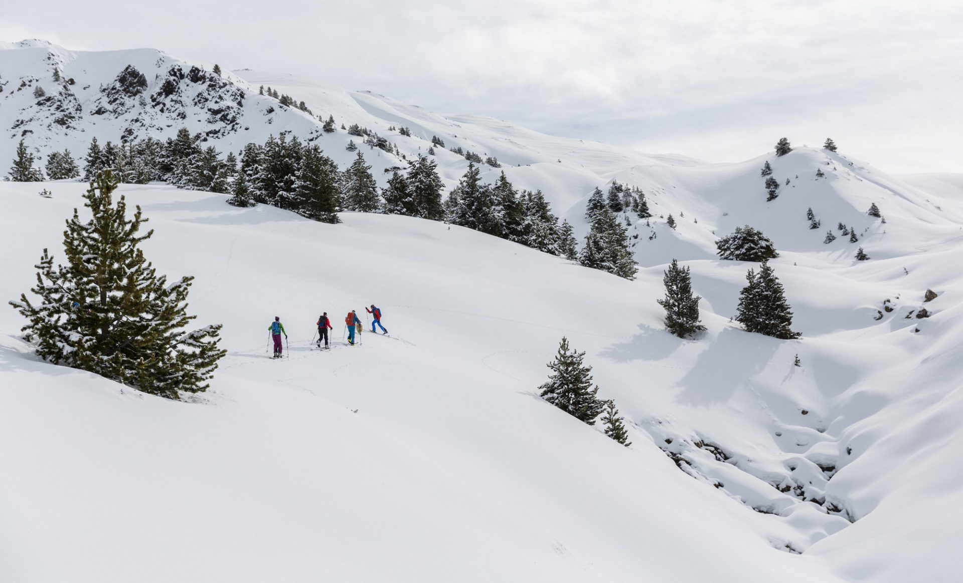 Four people skying uphill in a mountain area.