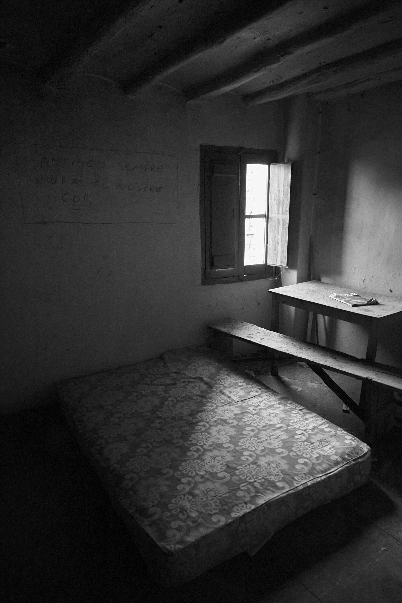 In a old room with a window open there is a mattress in the floor, a seat and a table with a magazine on it. A painting in the wall can be read, Santiago sempre viura al nostre cor. Black and white photography. Nostalgic.