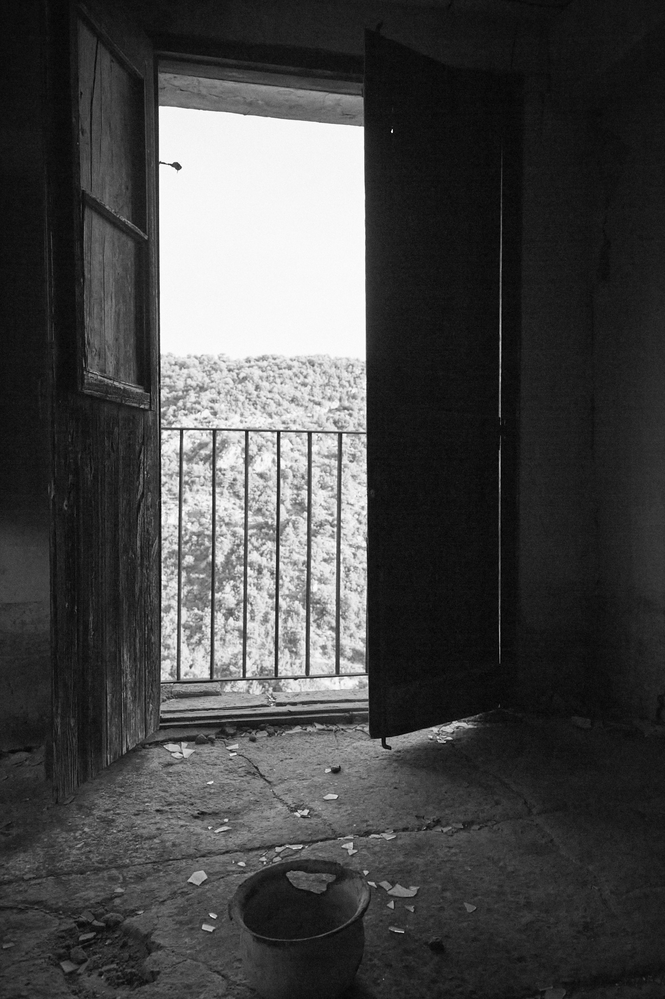 A room with an open window of an abandon house. There is a bucket with a hole and broken glass on the floor.