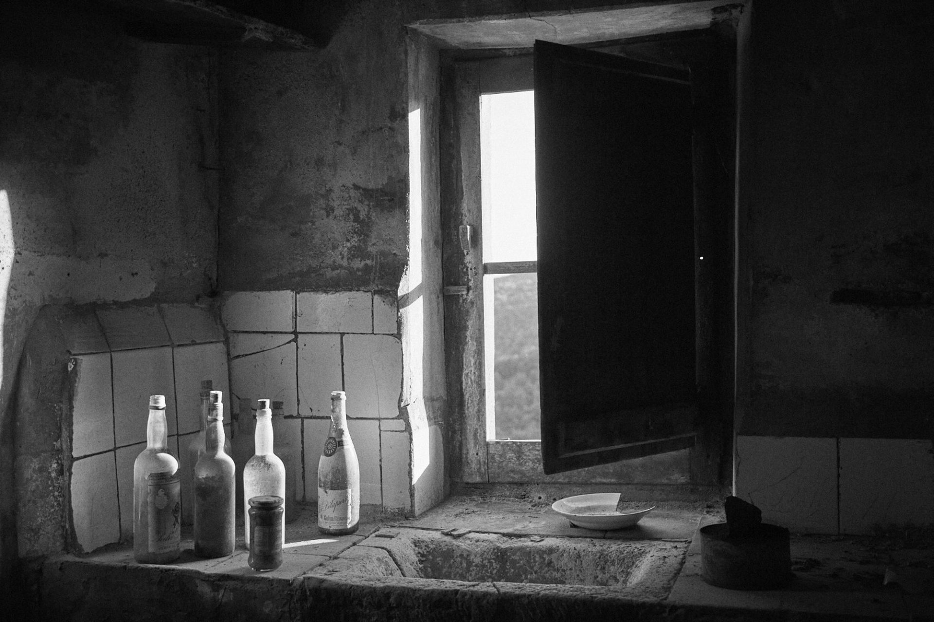 A window is open letting the lighting some old glass bottles in an abandon kitchen. Black and white photography. Nostalgic.