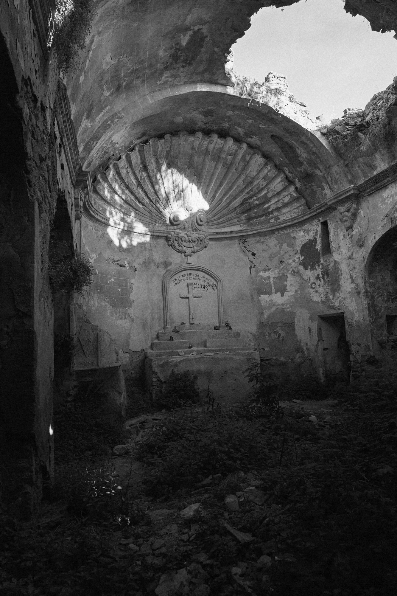 An abandon church with a hole in its roof. The altar has a cross and a shell shape.