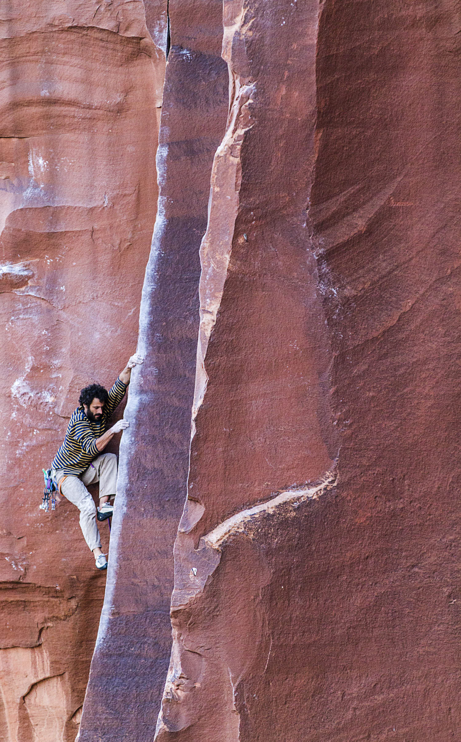 A bearded young man wearing a stripped sweeter rock climbing a colour red rock.