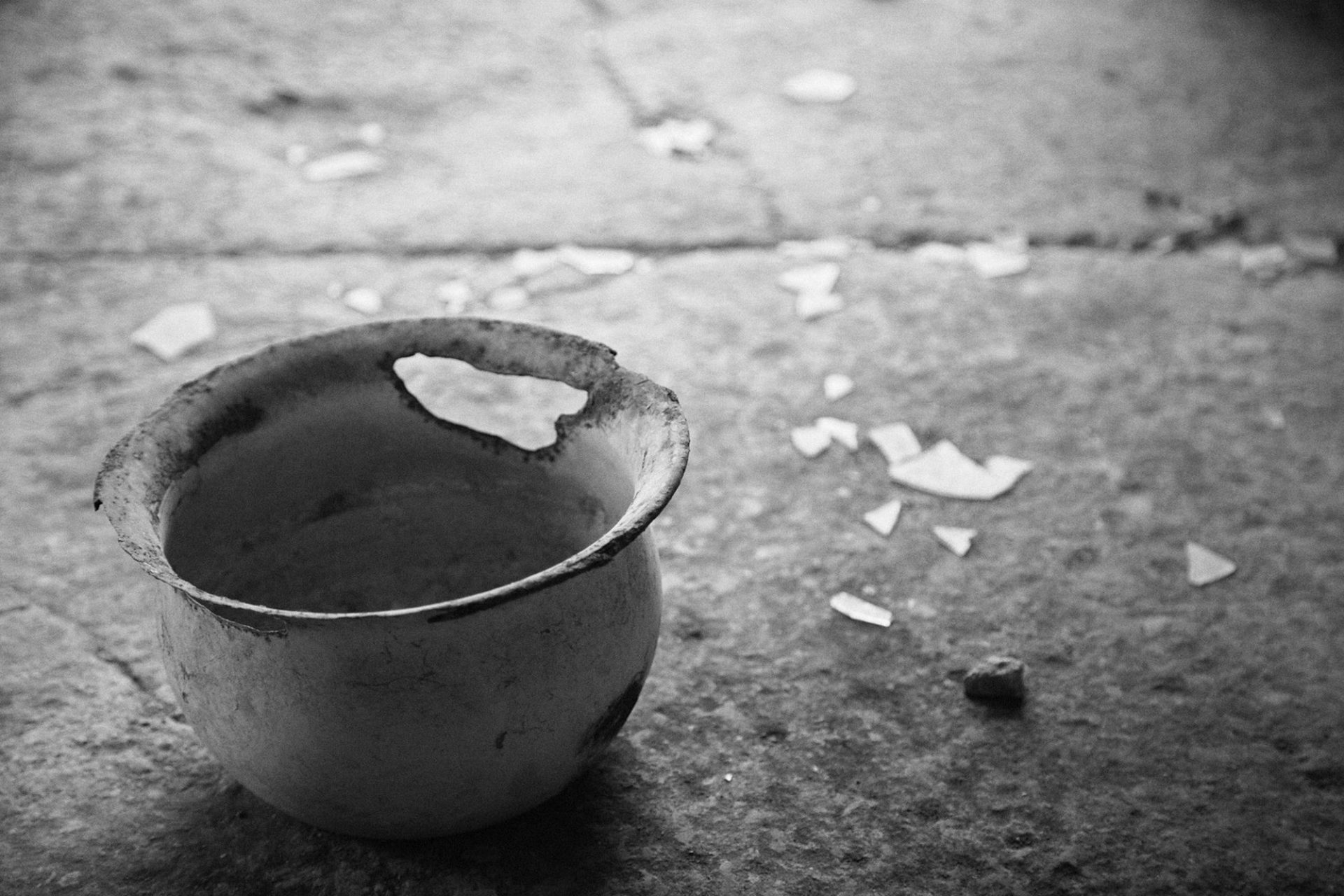 Detail of a metal bucket with a hole. There are broken glass parts on the floor. Black and white image. Nostalgic.
