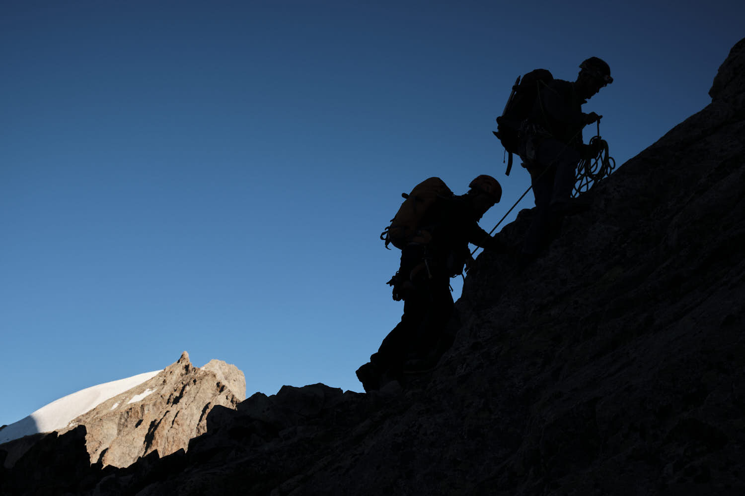 Two persons roped up together while they climb a mountain slope.