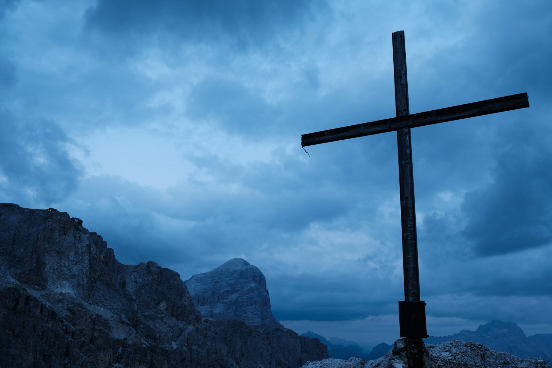 A cross in a mountain area at sunset with a blue clouds covered sky.