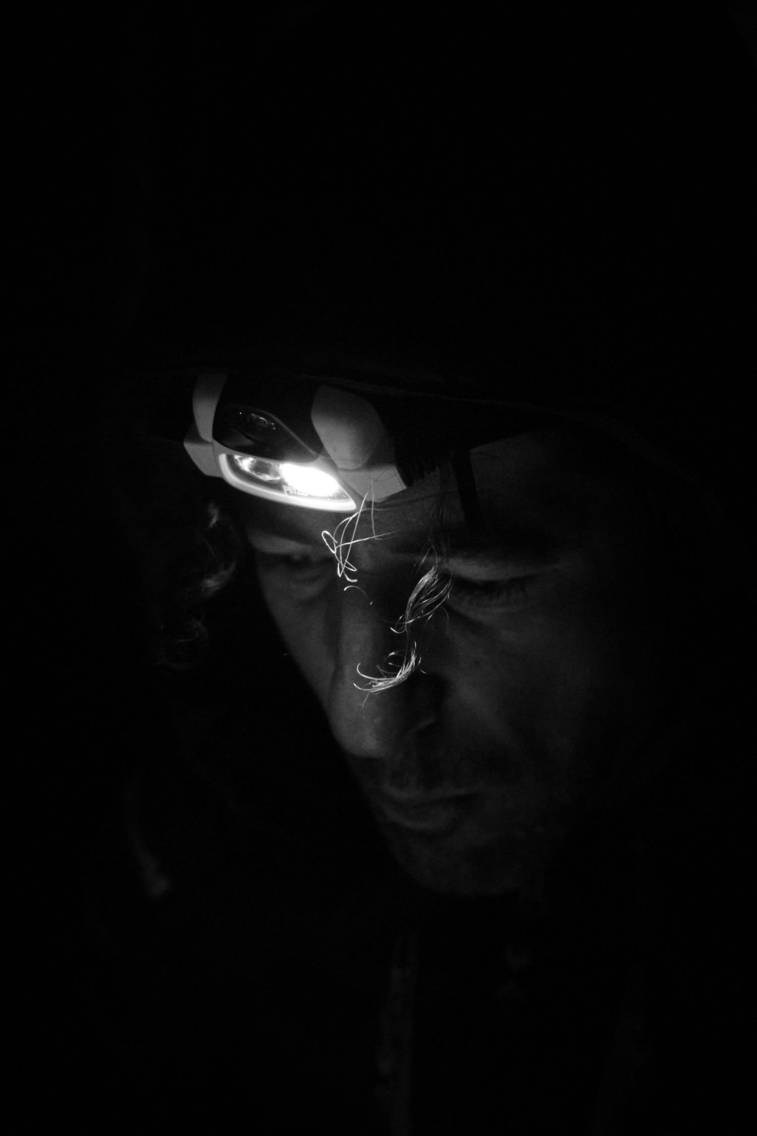 A headtorch iluminates a man face and part of his curly hair. Black and white photography.