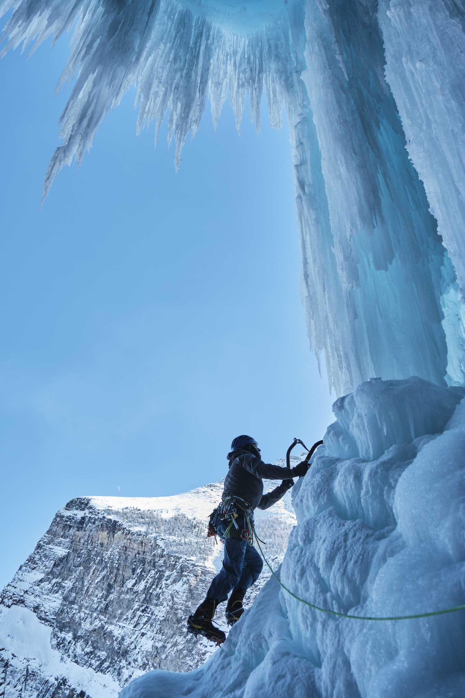 A person ice climbing a frozen water fall.