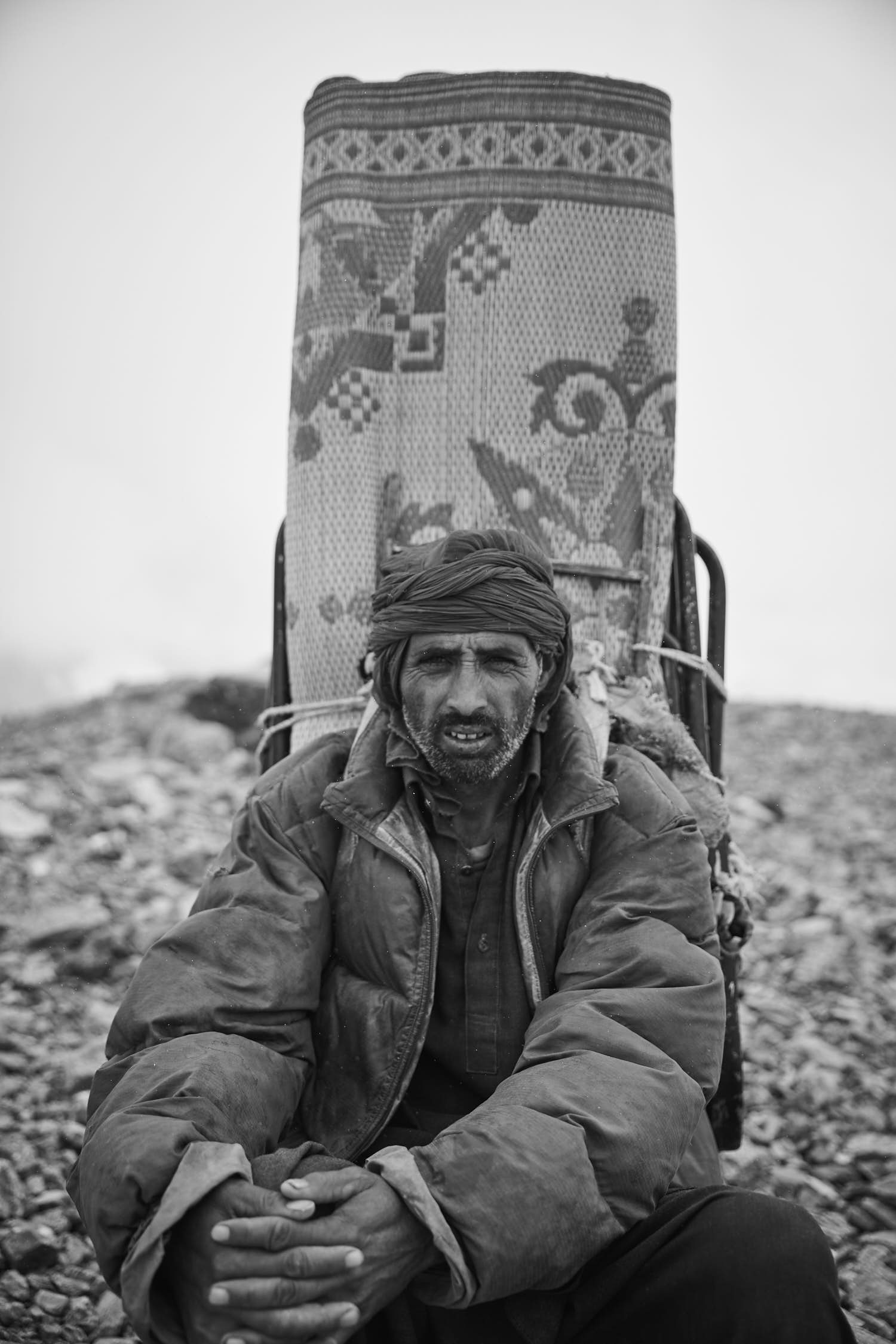 Portrait of a Balti porter carrying a big carpet. Black and white photography.