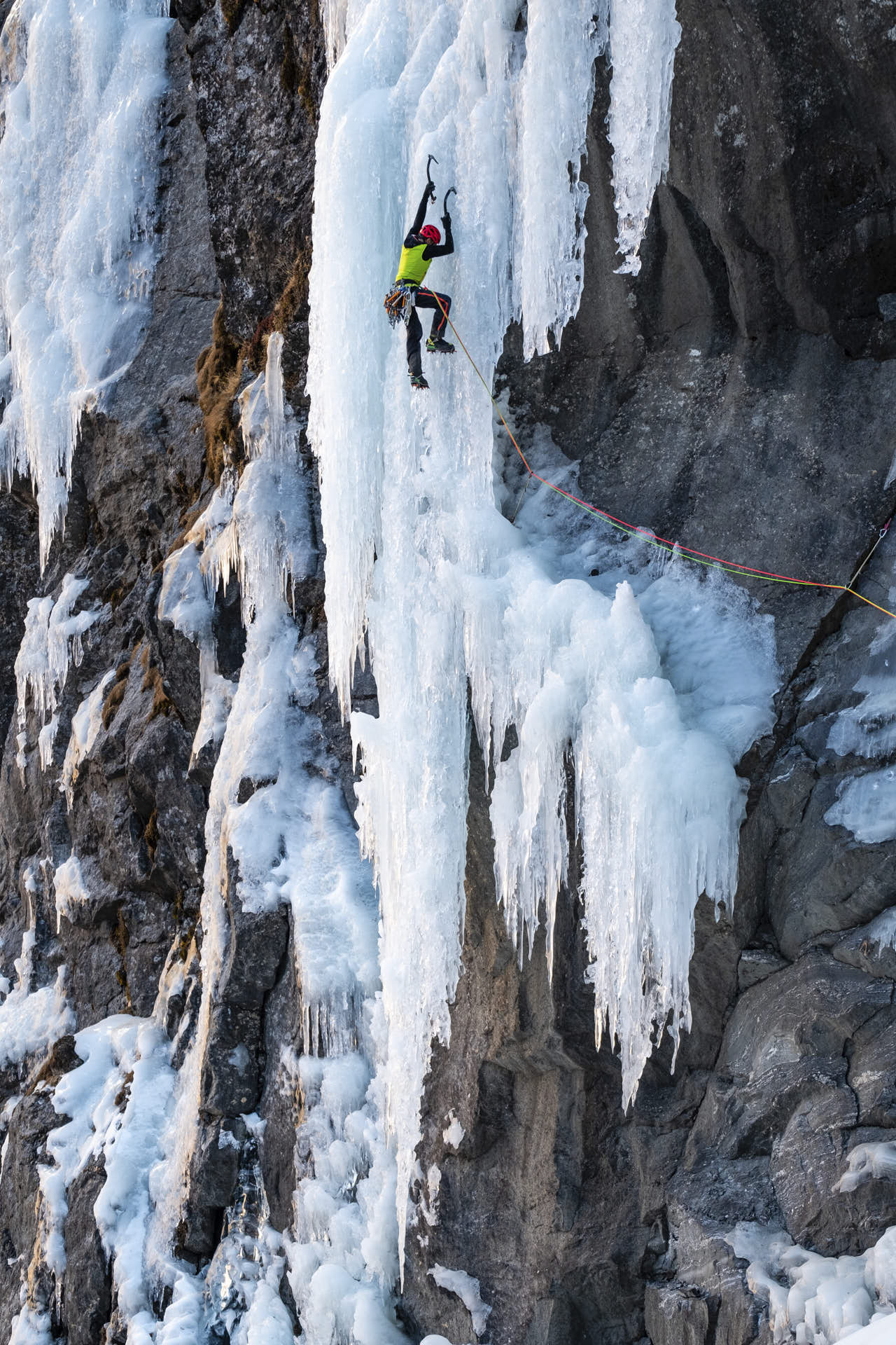 A person ice climbing a frozen water fall. Gravity.