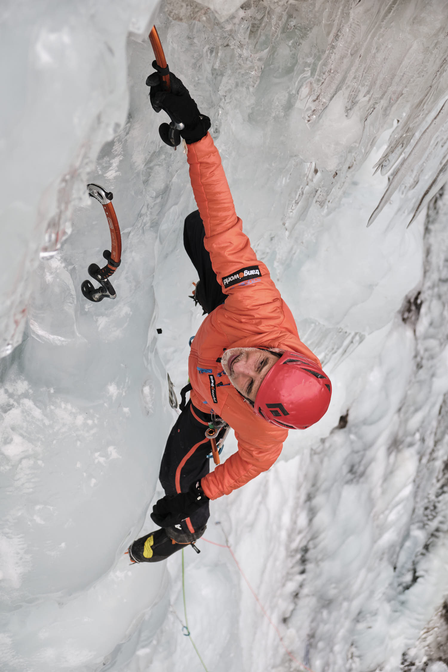 A man hanging from an ice axe while ice climbing an iced water fall.