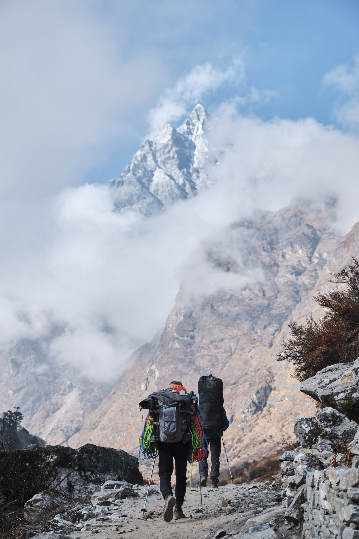 Two people carrying big backpacks in a mountain area.
