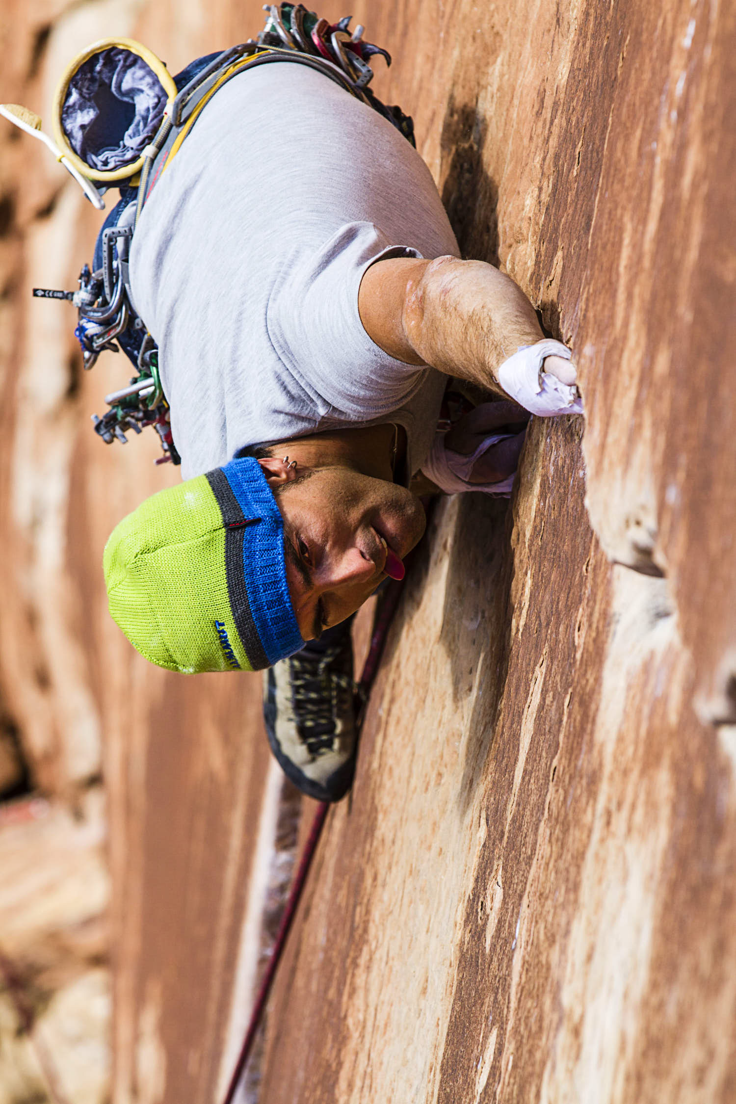 A young man rock climbing showing his tongue out of his mouth.