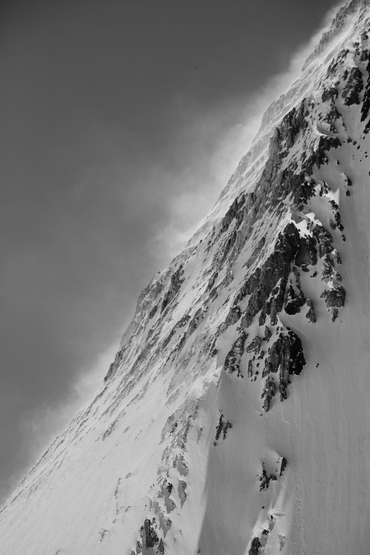 Three people ascending a mountain slope full of snow and rock. Black and white photography.
