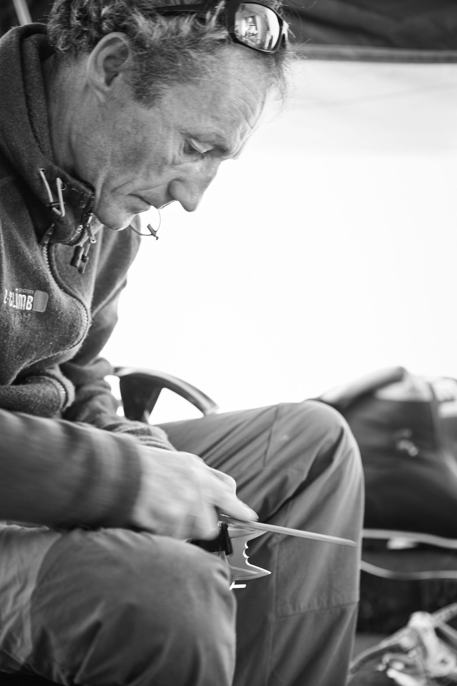Portrait of a man sharpening a crampon. Black and white photography.