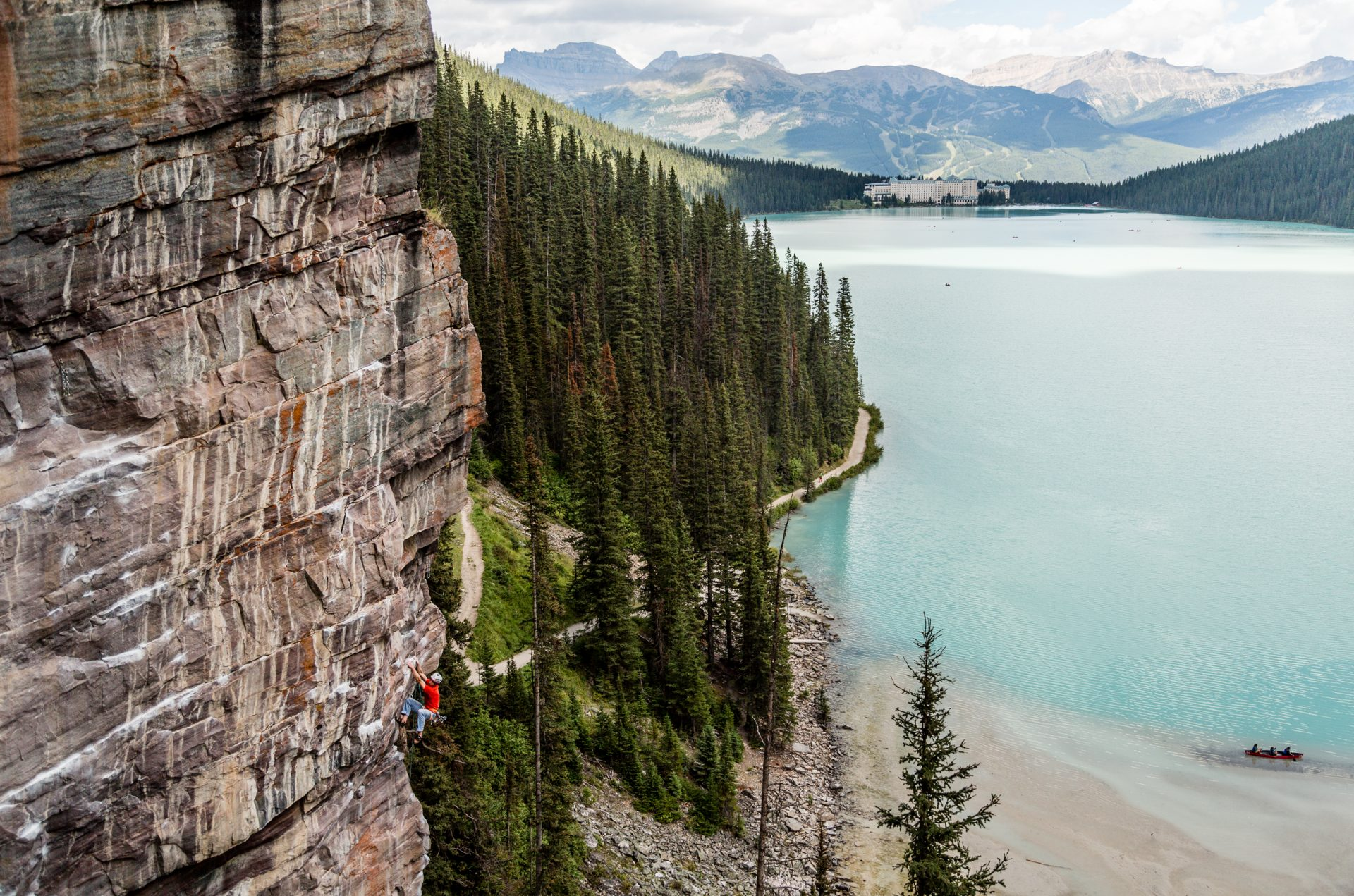 A man climbing a rock wall over a lake and forest trees.