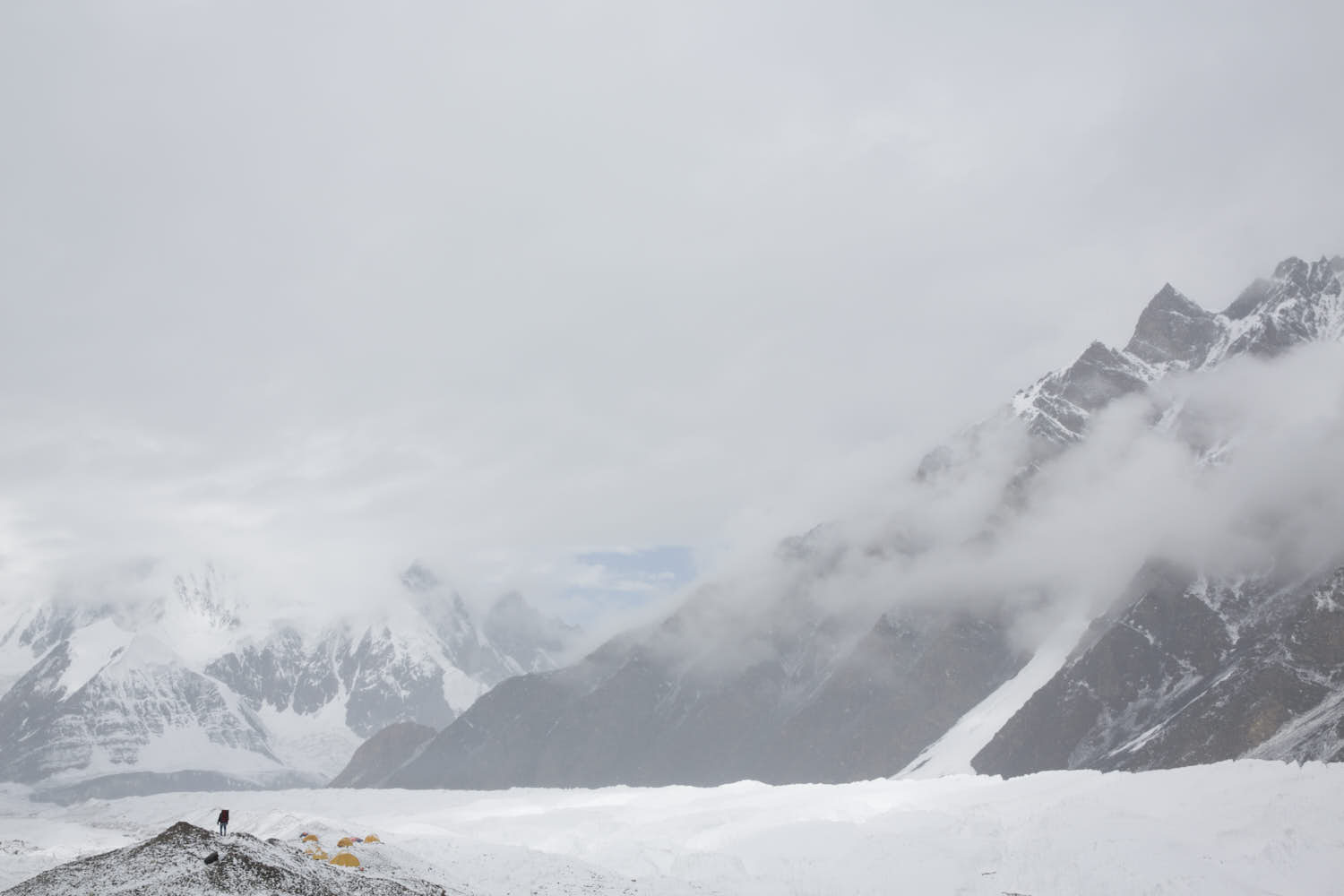 A person walking in a mountain edge next to a glacier covered in clouds.