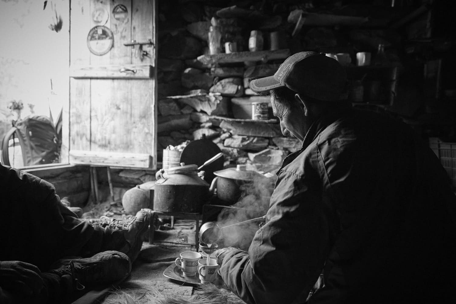 A man wearing a baseball cap serving tea in a rustic hut. Black and white photography.
