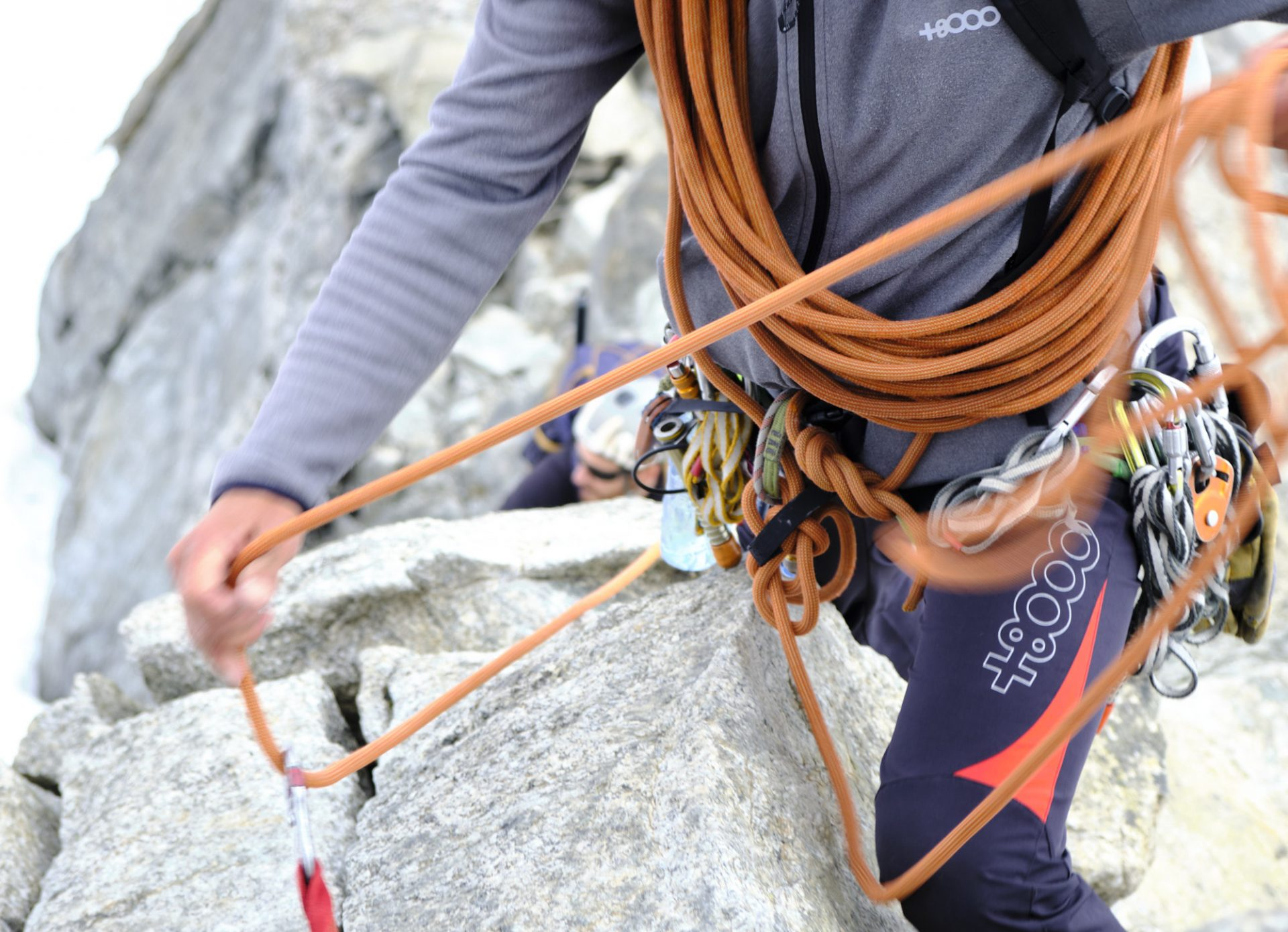 A person holding an orange climbing rope with both hands.