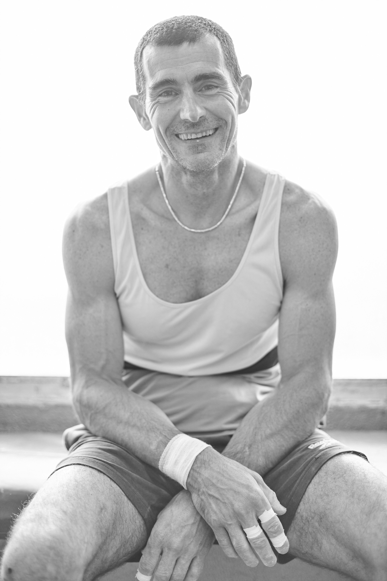 A climber smiling with his arms crossed on his legs.
