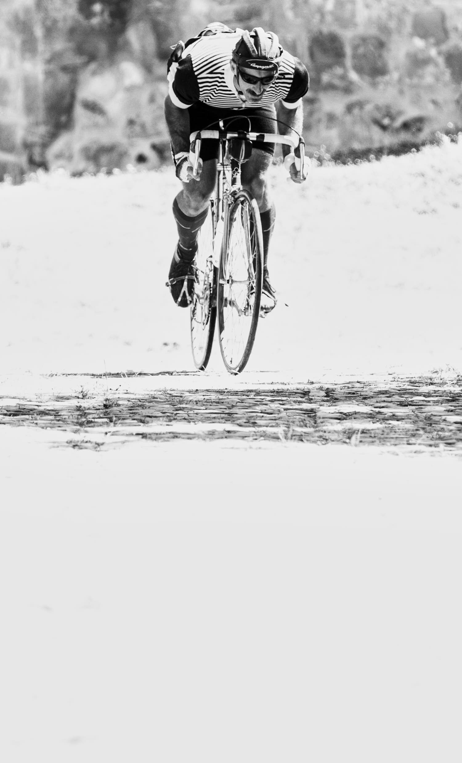 A cyclist wearing a classic retro outfit and riding a classic retro bike, ascending a cobble stone road.