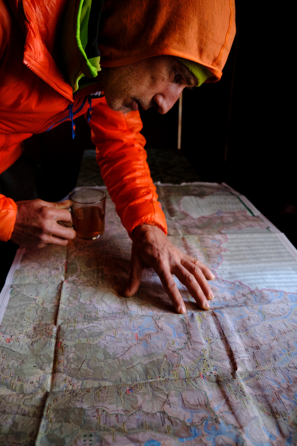A man holding a cup with a tea reading a map.