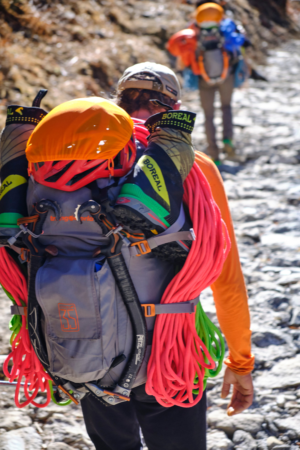 Two person carrying back packs with climbing equipment.