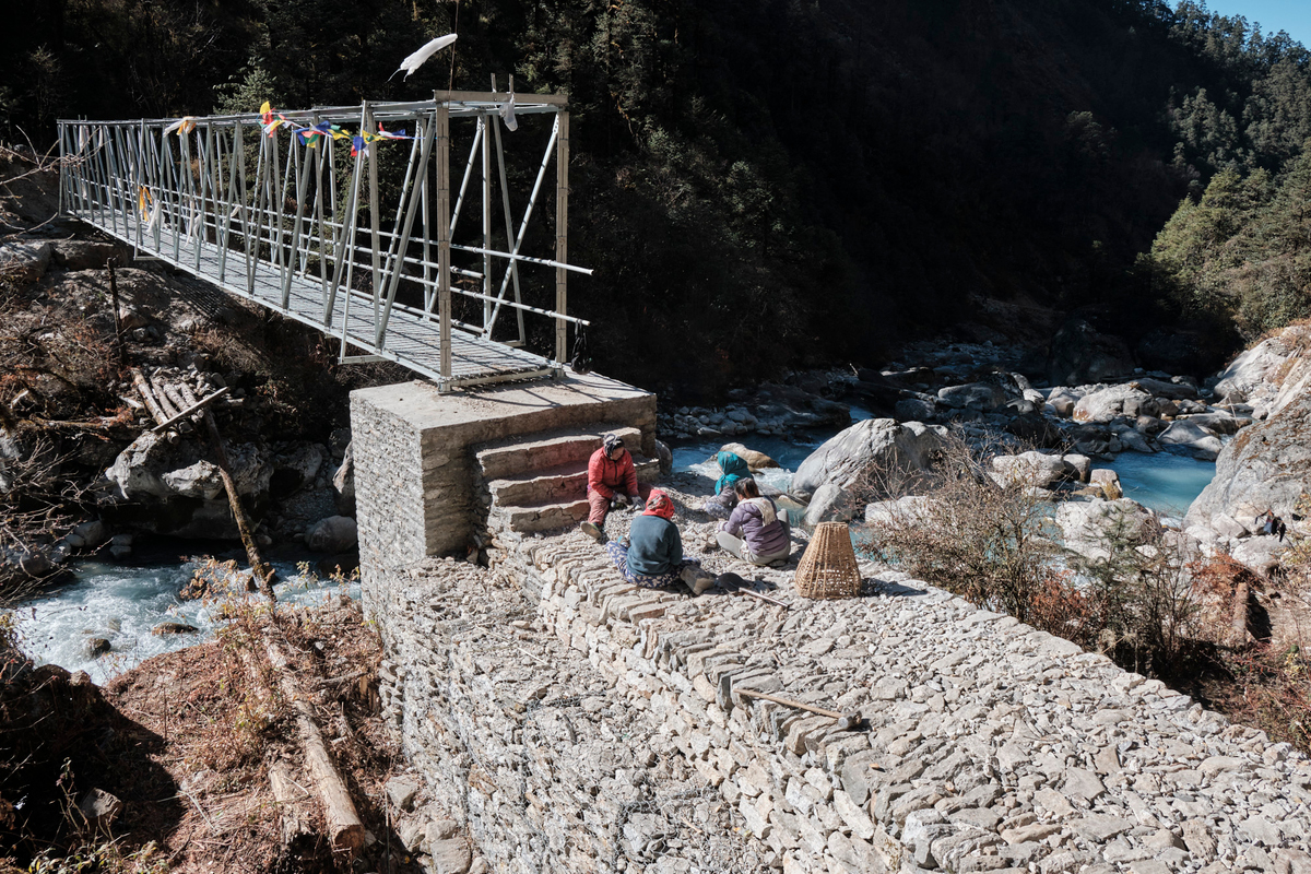 Four people sitting next to a bridge made of stone and metal.