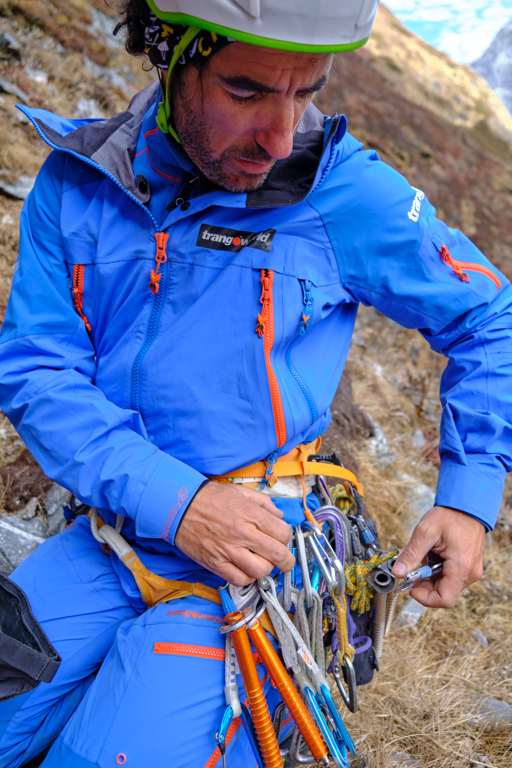 A man arranging in the harness ice climbing equipment.