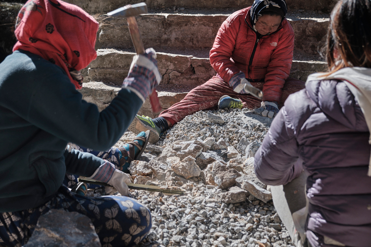 Three woman cutting stones by hitting rocks with hammers.