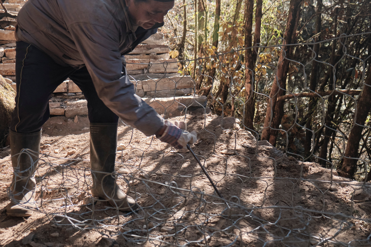 A man with a metal tool doing cages with wire mesh.