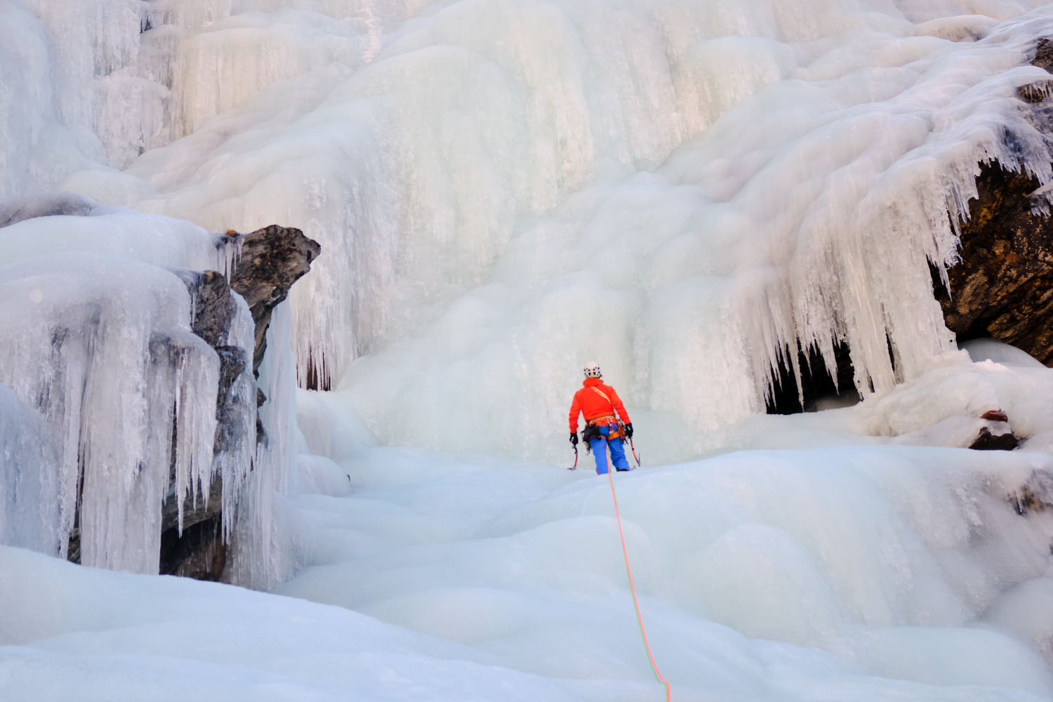 A climber holding ice axes facing a frozen water fall.