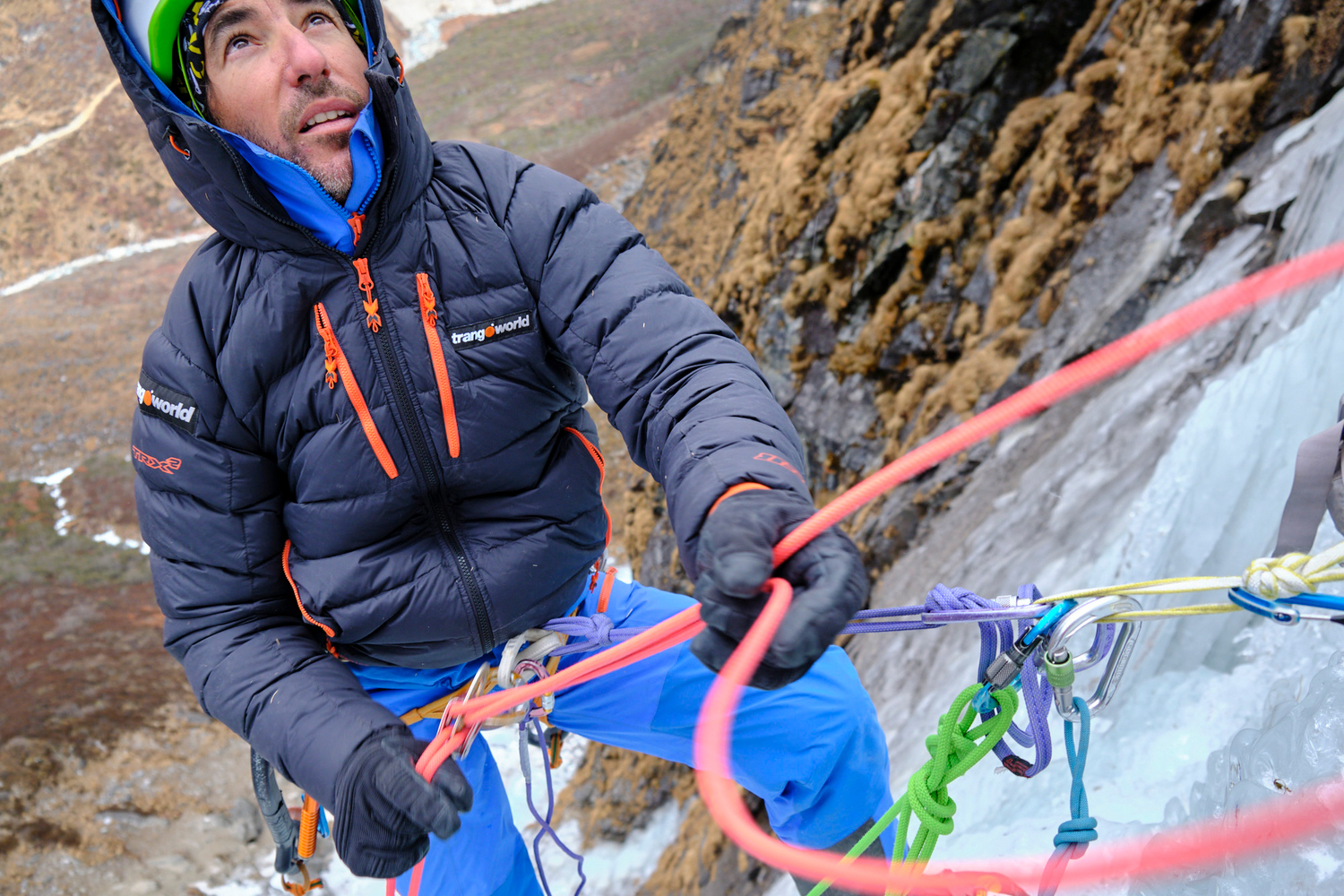 A man belaying in an ice fall.