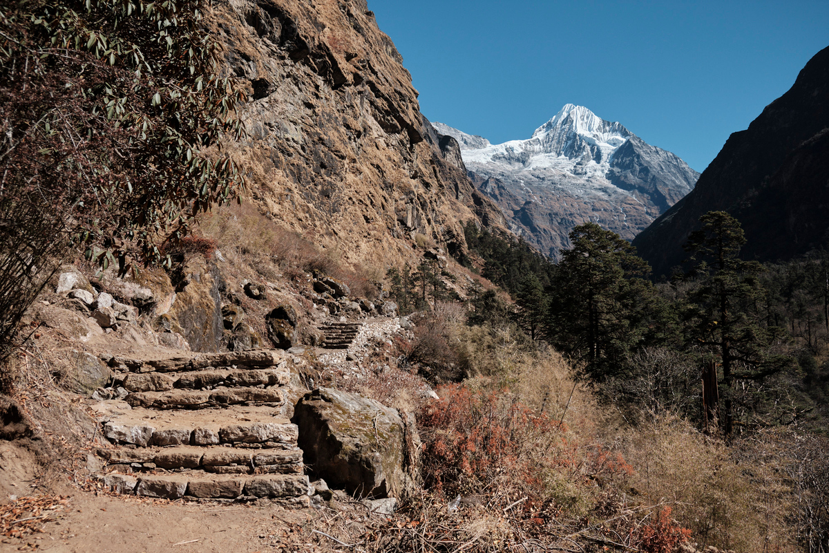 A mountain path with steps made of stone and a mountain cover in snow in the background.