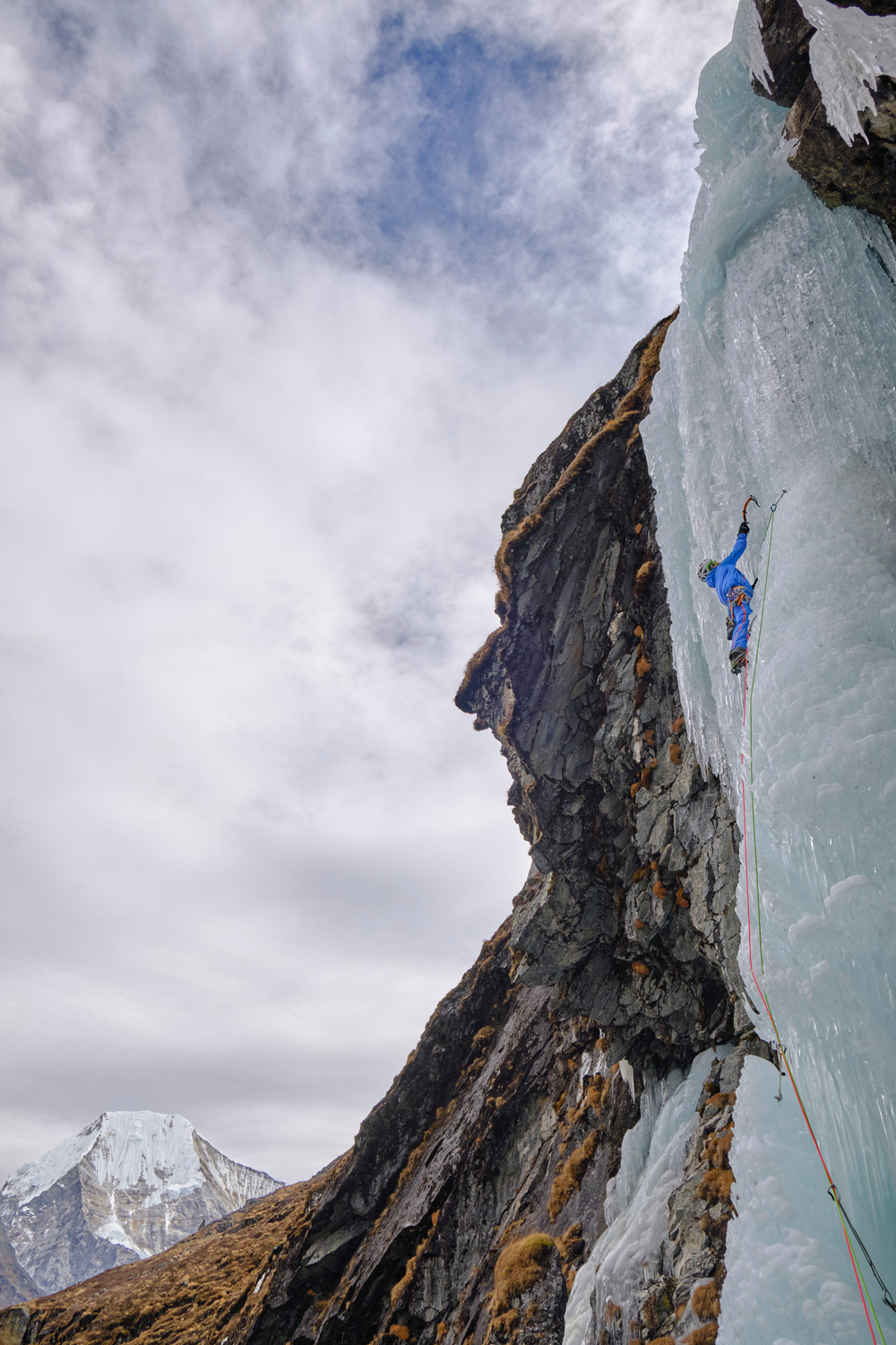 A climber ice climbing a frozen water fall.