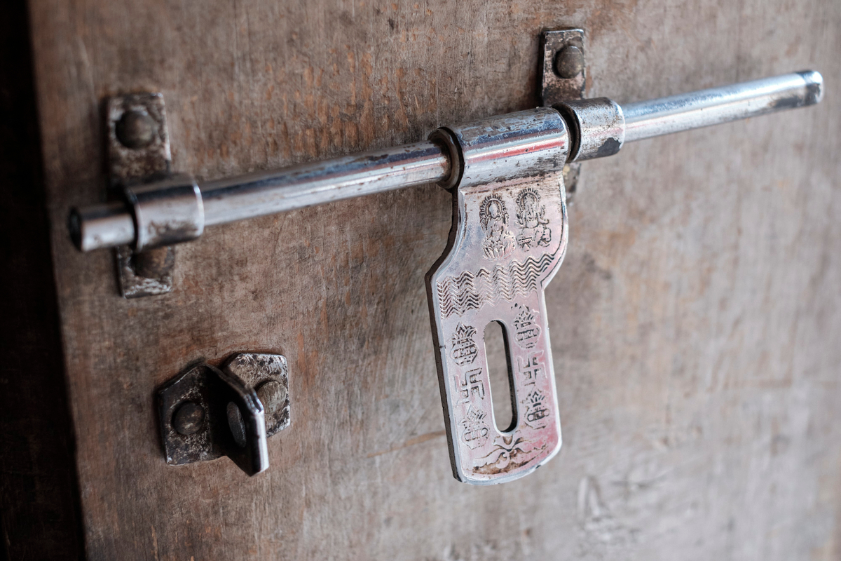 Detail of a door lock with Buddhist symbols.