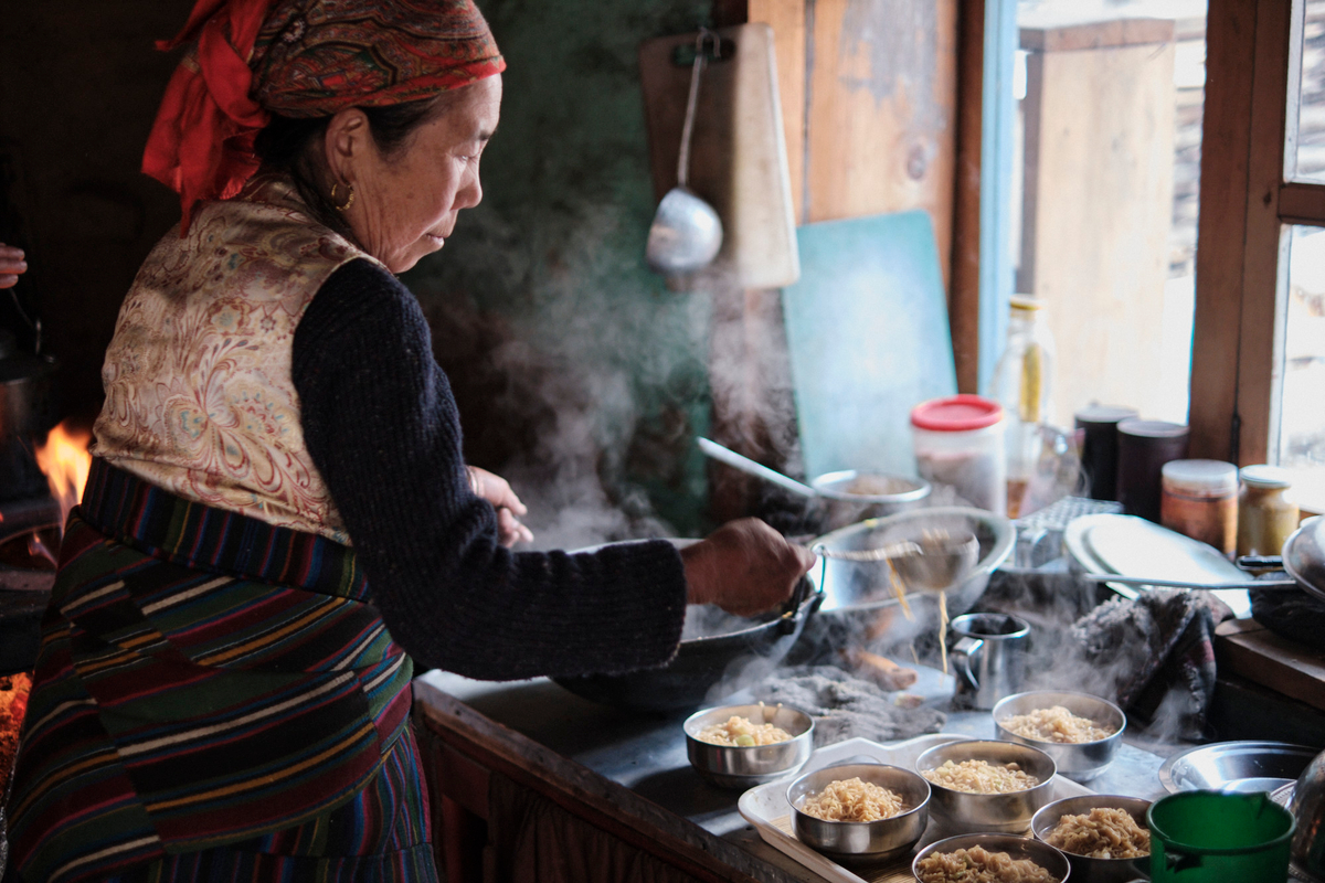 A woman wearing traditional Nepali clothes prepares several noodles dishes.