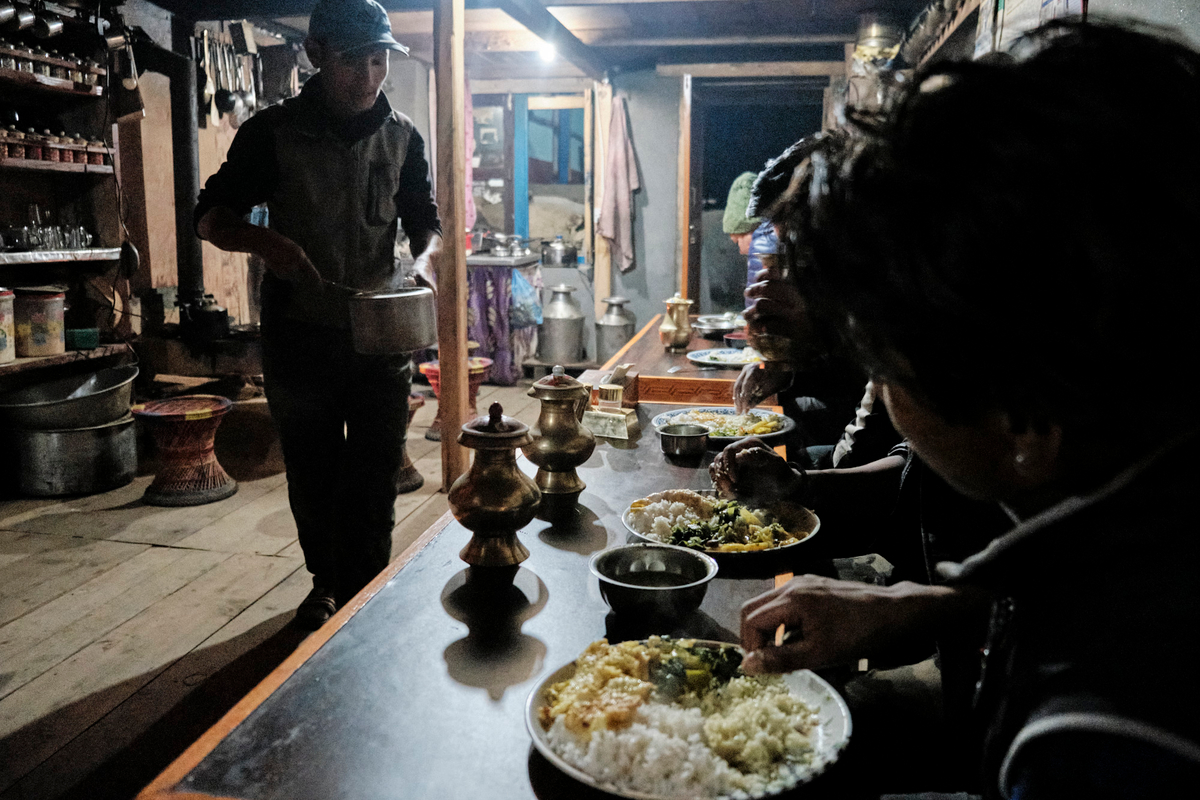 A man with a pot serving food to people who eat with their hands.