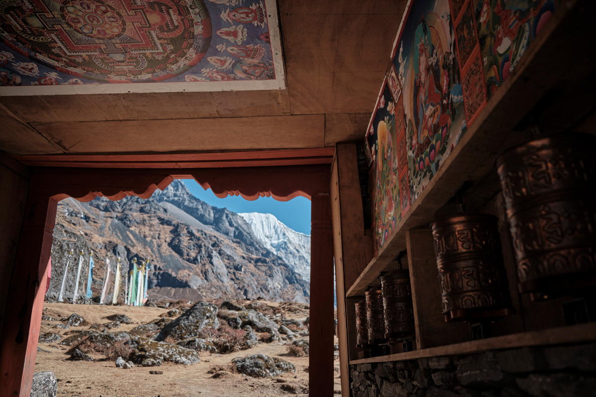 Buddisht prayer rolls in a entry house with mountains in the background.
