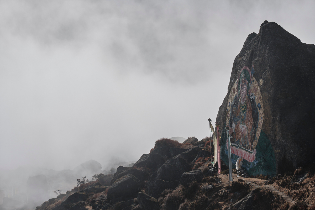 A paint of Guru Rimpoche sculpted in rock next to mantras in flags.