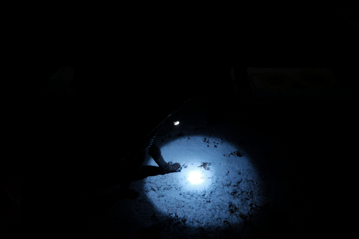 A person with a light that creates a circle walking on a snow covered ground.