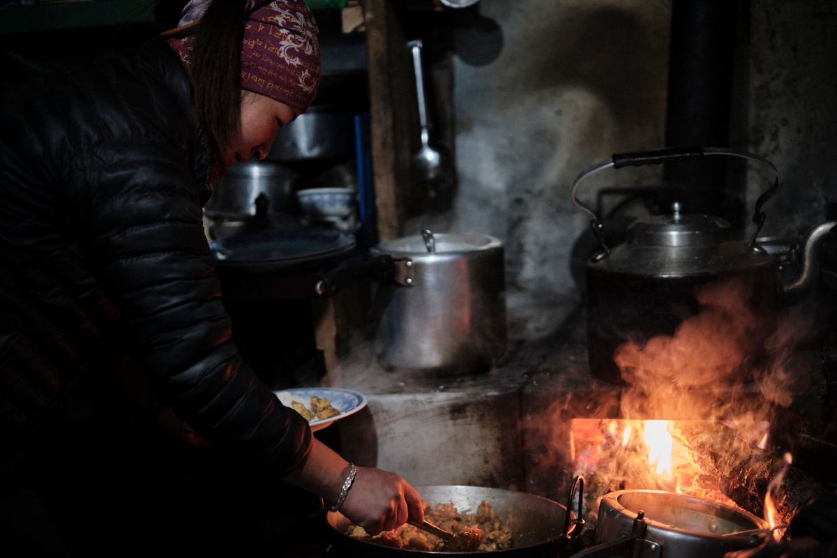 A woman cooking with a wok.