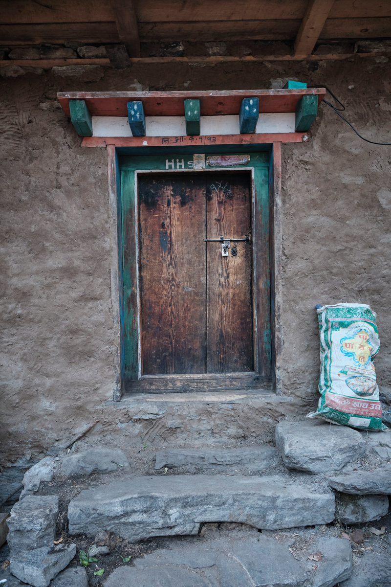 The main door made of wood with a rice sack next to it.
